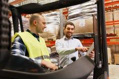 Hommes heureux avec le PC et le chariot élévateur de comprimé à l'entrepôt Photographie stock libre de droits