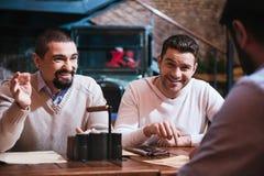 Hommes heureux gais discutant quelque chose Images stock