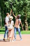 Hommes heureux multi-ethniques donnant la haute cinq en parc Images libres de droits