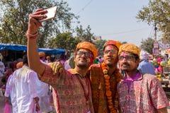 Hommes indiens non identifiés couverts de couleurs faisant la photo de selfie pendant la célébration de Holi dans Vrindavan Images libres de droits