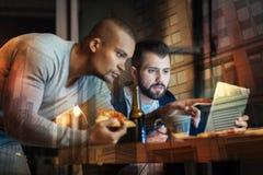 Hommes inquiétés regardant l'écran et se sentant étonnés Image stock