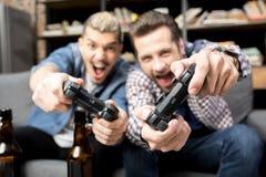Hommes jouant avec des manettes Photos stock
