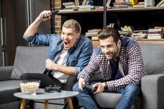 Hommes jouant avec des manettes Images stock