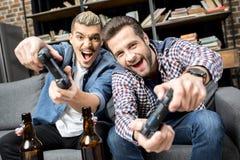 Hommes jouant avec des manettes Photographie stock libre de droits