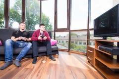 Hommes jouant des jeux vidéo tout en se reposant sur le sofa Photographie stock