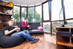 Hommes jouant des jeux vidéo tout en se reposant sur le sofa Images libres de droits