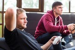 Hommes jouant des jeux vidéo tout en se reposant sur le sofa Photographie stock libre de droits