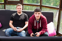 Hommes jouant des jeux vidéo tout en se reposant sur le sofa Image libre de droits