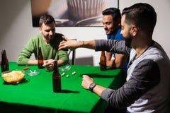 Hommes jouant des matrices et buvant de la bière Photographie stock libre de droits