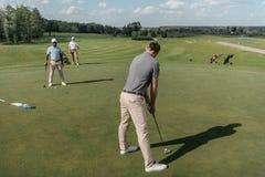 Hommes jouant ensemble sur le terrain de golf à la journée Photographie stock libre de droits