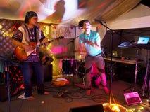 Hommes jouant la guitare et les dispositifs trembleurs jouant sur l'étape photo libre de droits