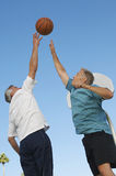 Hommes jouant le basket-ball contre le ciel bleu Photos stock