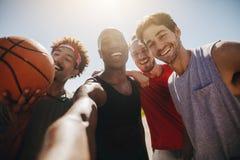 Hommes jouant le basket-ball posant pour la photo Photos stock