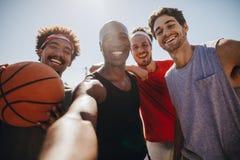 Hommes jouant le basket-ball posant pour la photo Images libres de droits