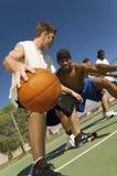 Hommes jouant le basket-ball sur la cour Image libre de droits