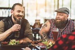 Hommes joyeux adultes passant la soirée dans la barre Image libre de droits