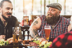 Hommes joyeux agréables s'asseyant à la table Photos stock