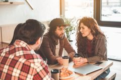 Hommes joyeux et femmes buvant du café ensemble en café Images stock