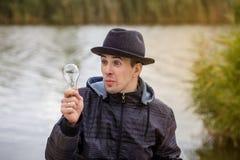 Hommes jugeant l'ampoule électrique Photographie stock