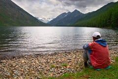Hommes, lac et montagnes. Photographie stock