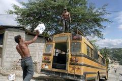 Hommes latins chargeant l'autobus de toit avec des boîtes Image libre de droits