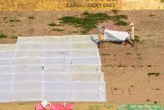 Hommes lavant des vêtements sur les ghats de Varanasi Images libres de droits
