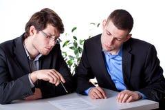 Hommes lisant un contrat avant la signature Image libre de droits