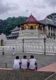 Hommes locaux s'asseyant au temple sacré de relique de dent image stock