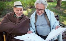 Hommes mûrs heureux lisant le journal en parc Image libre de droits