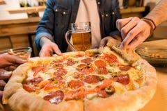 Hommes mangeant de la pizza Photographie stock