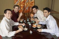 Hommes mangeant des sushi avec des baguettes dans le restaurant Photo stock