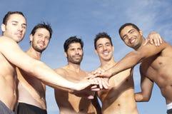 Hommes mettant leurs mains sur chaque autres mains Image stock