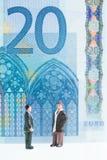 Hommes miniatures causant avec le fond de billet de banque de l'euro 20 Photographie stock