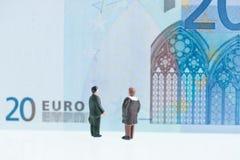 Hommes miniatures regardant la fin de fond de billet de banque de l'euro 20  Photographie stock libre de droits
