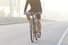 Hommes montant des bicyclettes sur la brume de pont Images stock