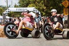 Hommes montant la course adulte de grandes roues au festival Images stock