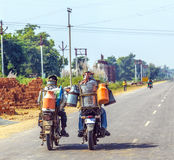 Hommes montant la motocyclette avec des boîtes Photo stock