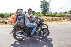 Hommes montant la motocyclette avec des boîtes Image libre de droits
