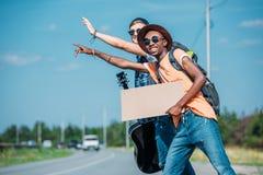 hommes multi-ethniques avec le carton vide saluant la voiture d'arrêt tout en faisant de l'auto-stop Photos libres de droits