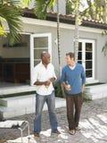 Hommes multi-ethniques ayant la conversation sur le patio Photographie stock libre de droits