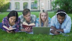 Hommes multi-ethniques et femmes faisant le travail sur l'herbe sur le campus, enseignement supérieur clips vidéos