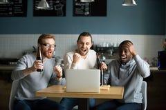 Hommes multiraciaux buvant de la bière célébrant le jeu de observation de victoire Photographie stock libre de droits