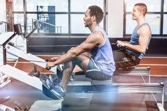 Hommes musculaires à l'aide de la machine à ramer images stock