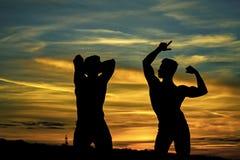 Hommes musculaires dans le coucher du soleil avec des boîtes Photographie stock libre de droits