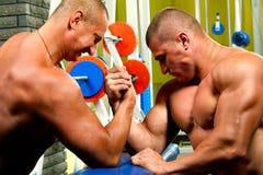 Hommes musculaires mesurant des forces Photos stock