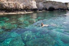 Hommes nageant en clair la lagune de la mer Méditerranée Photo stock