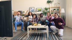 Hommes nerveux et femmes observant des sports à la TV se sentant triste et déçue banque de vidéos