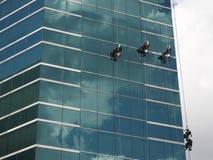 hommes nettoyant le bâtiment en verre par l'accès de corde à la taille Photo stock