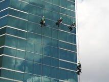 hommes nettoyant le bâtiment en verre par l'accès de corde à la taille photographie stock