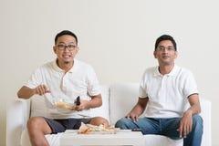 Hommes observant la manifestation sportive vivante à la TV ensemble Images libres de droits